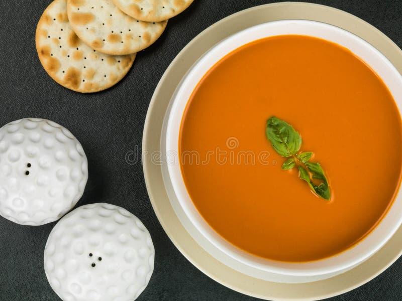 Bacia biscoitos do biscoito de água do tomate e do Basil Soup With e sal e pimenta imagens de stock royalty free