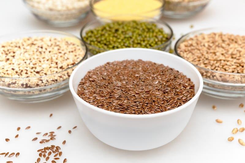 Bacia branca com as sementes de linho no fundo borrado dos copos com cereais imagem de stock royalty free