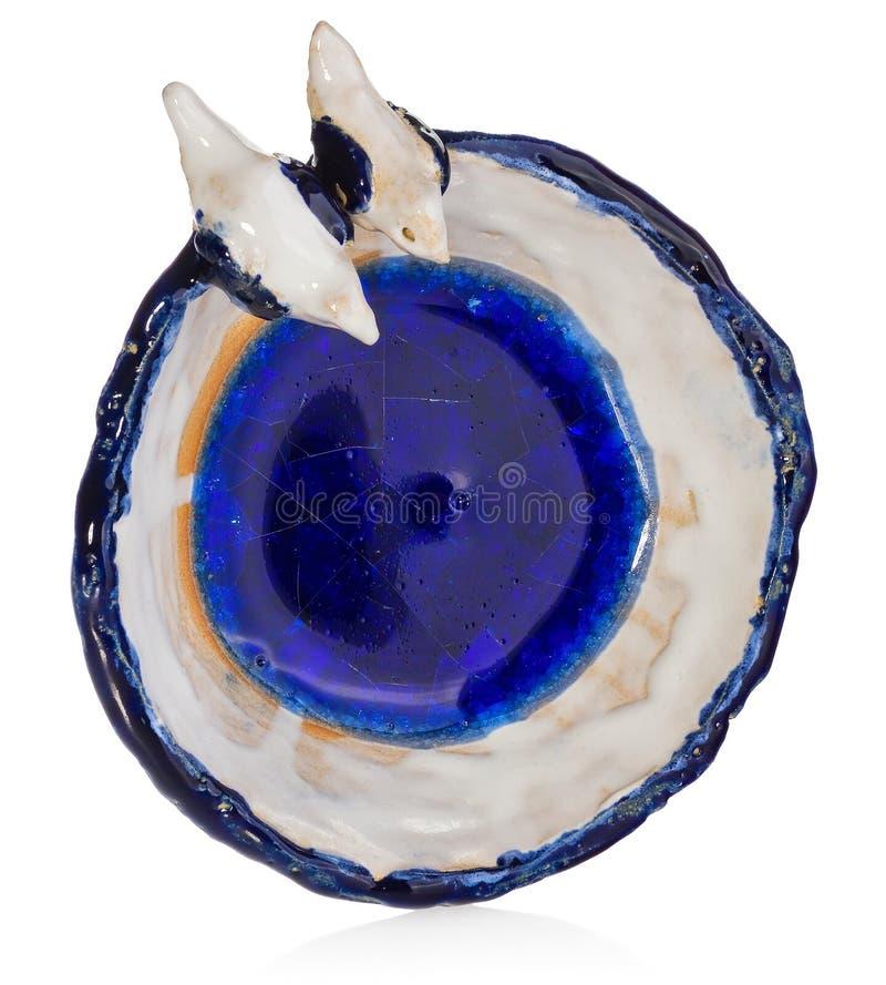 Bacia cerâmica feito a mão com os dois pássaros no amor na borda do prato O copo no azul da cor, azul marinho, branco, amarelo, c foto de stock