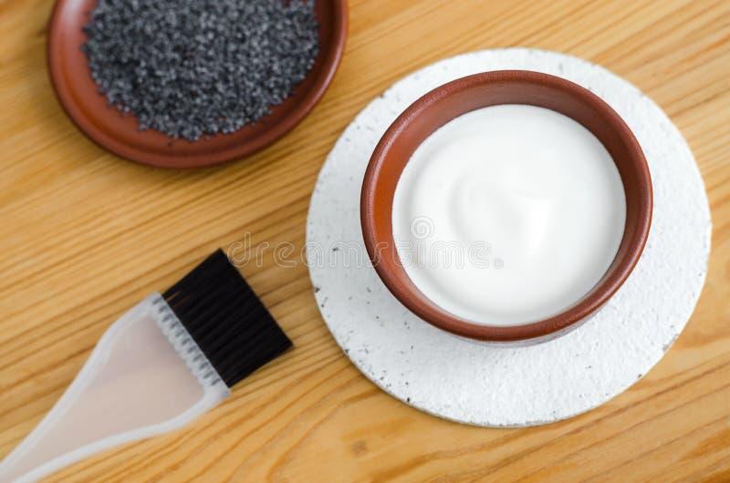 Bacia cerâmica pequena com as sementes gregas do iogurte e de papoila do creme de leite Os ingredientes para preparar a máscara f fotografia de stock
