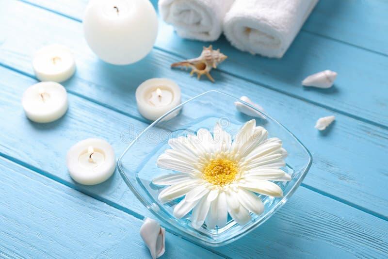 Bacia com água e velas aromáticas na tabela de madeira no salão de beleza dos termas foto de stock royalty free