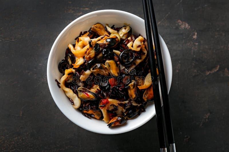 Bacia com arroz e marisco fervidos na tabela escura imagens de stock