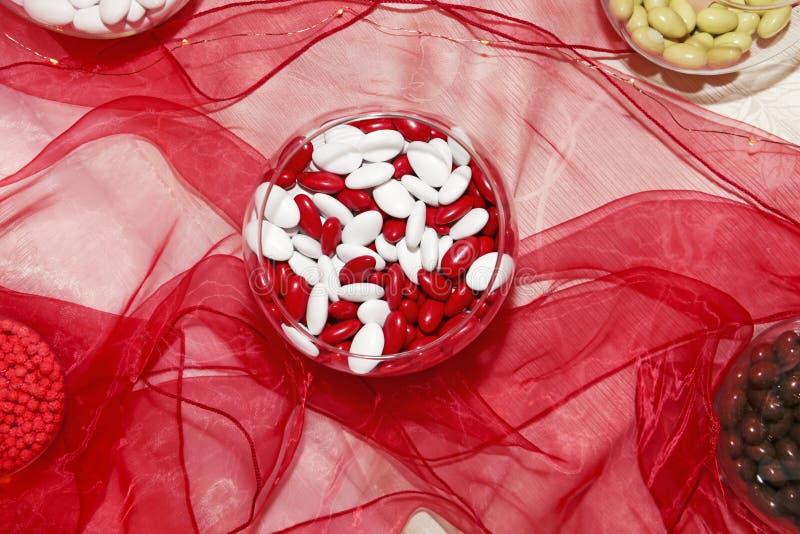 Bacia com as amêndoas adoçadas vermelhas e brancas em uma tabela do partido com sedas foto de stock