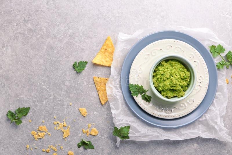 Bacia com as microplaquetas saborosos do guacamole e de tortilha na tabela foto de stock royalty free