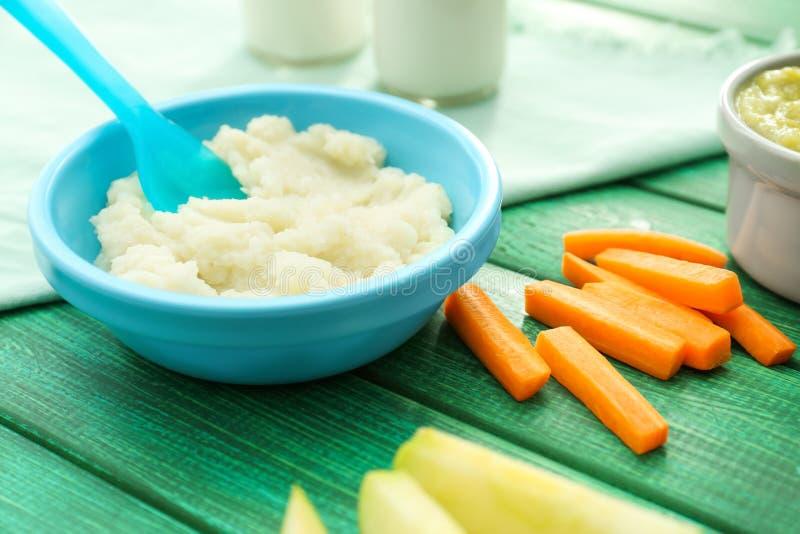 Bacia com comida para bebê saudável na mesa de cozinha imagem de stock