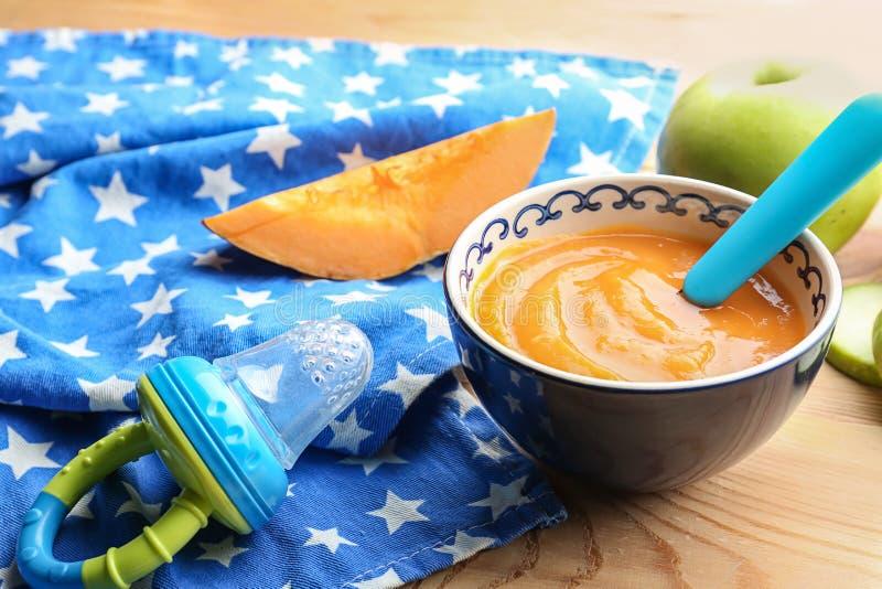 Bacia com comida para bebê saudável na tabela de madeira fotos de stock royalty free