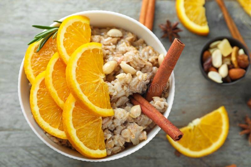 Bacia com farinha de aveia saboroso, a laranja cortada e as varas de canela na tabela de madeira imagens de stock