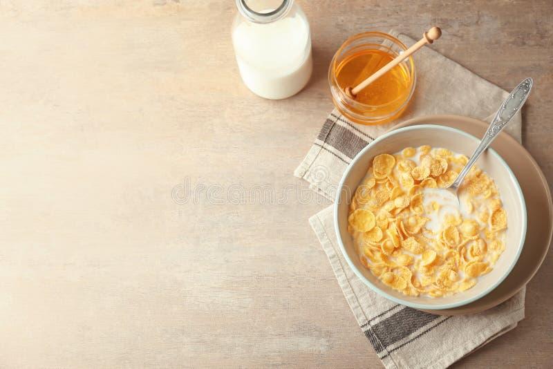 Bacia com flocos de milho, leite e mel saudáveis na tabela clara fotografia de stock