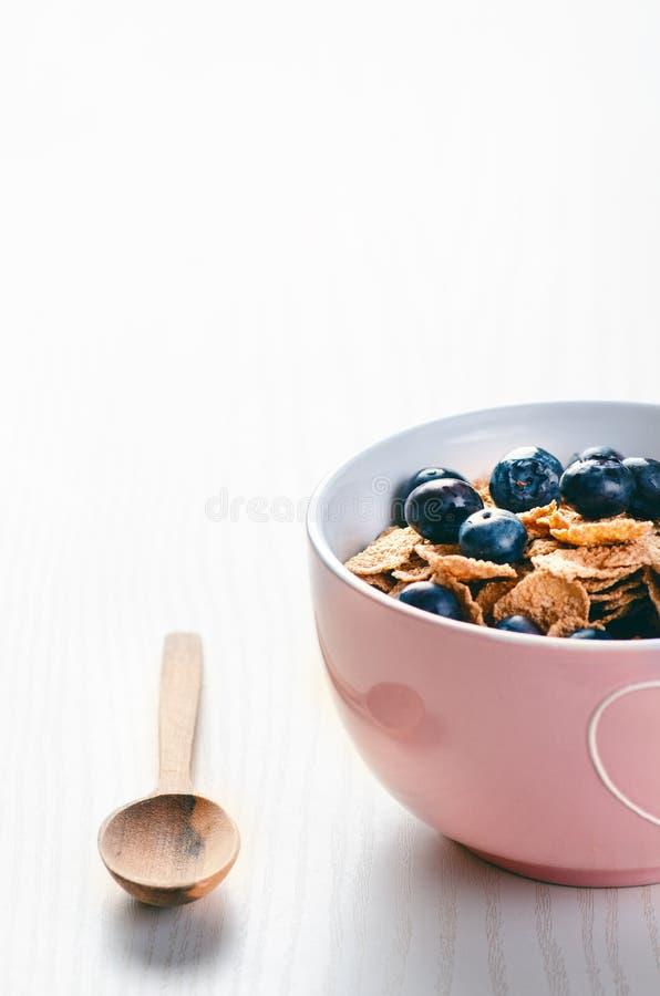 Bacia completa do muesli em uma tabela branca com mirtilo Cereais de café da manhã saudáveis com leite, semente, fruto Flocos da  fotografia de stock royalty free