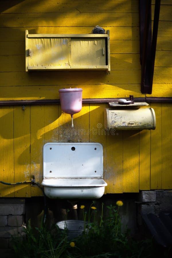 Bacia cor-de-rosa na parede amarela de uma casa de campo imagem de stock royalty free