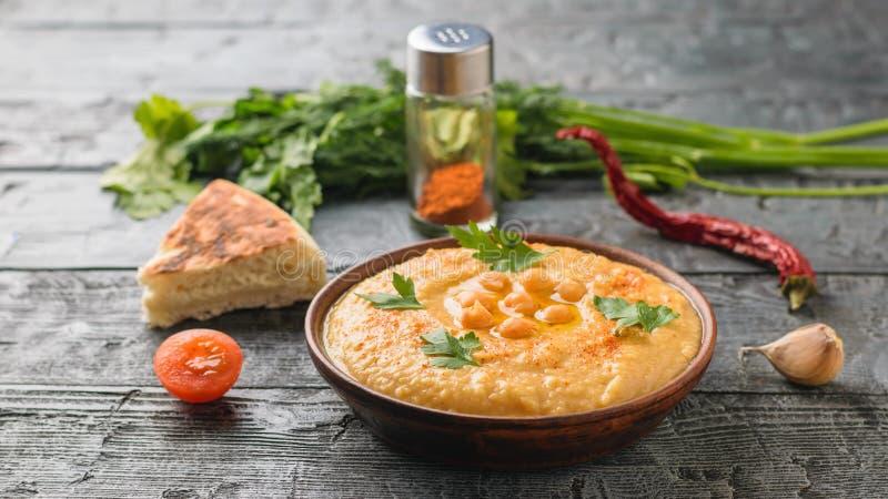 Bacia da argila com hummus fresco, uma parte de pão do pão árabe e tomates cortados em uma tabela de madeira escura foto de stock