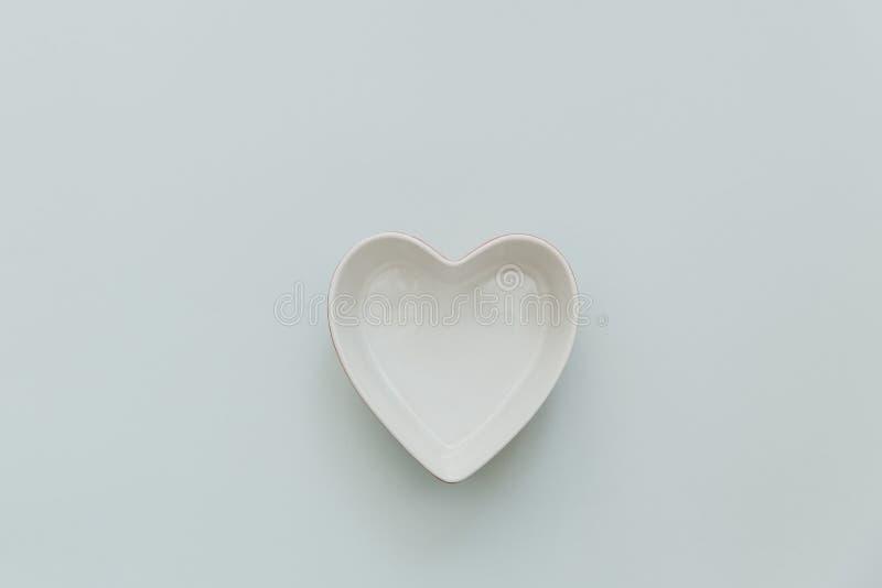 Bacia da forma do coração no fundo pastel fotografia de stock royalty free