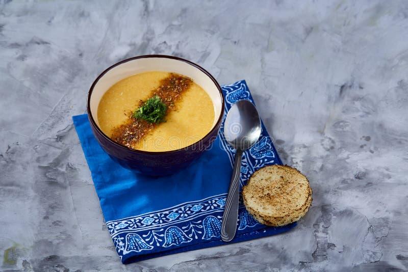 Bacia da porcelana de sopa da abóbora no guardanapo sobre o fundo textured branco, close-up, foco seletivo, vista superior foto de stock