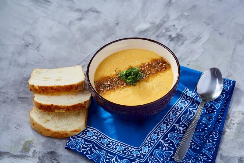 Bacia da porcelana de sopa da abóbora no guardanapo sobre o fundo textured branco, close-up, foco seletivo, vista superior imagem de stock