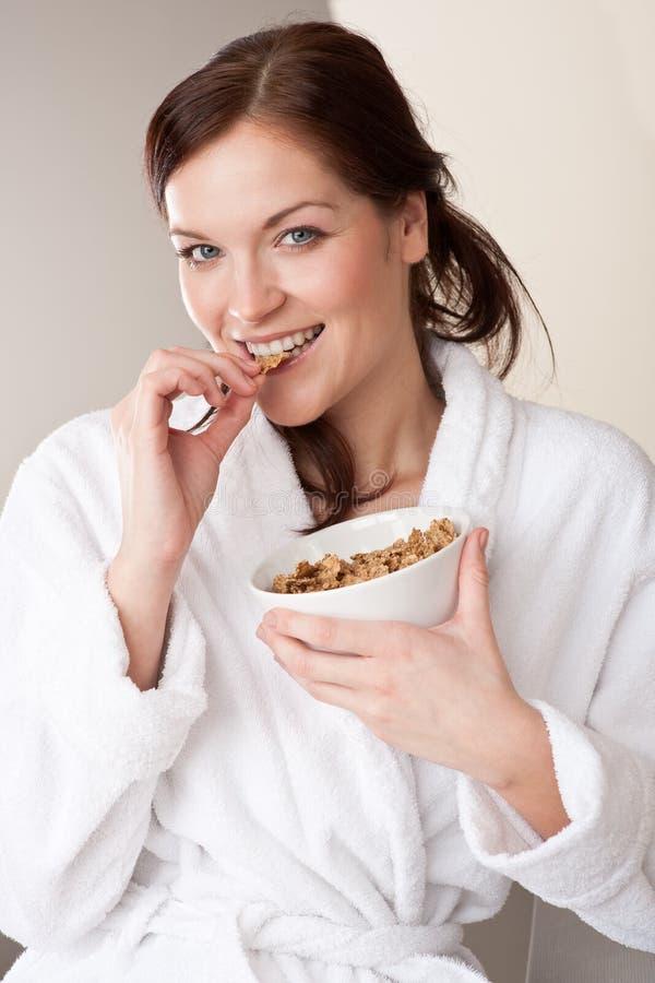 Bacia da terra arrendada da mulher com cereais para o pequeno almoço imagem de stock royalty free