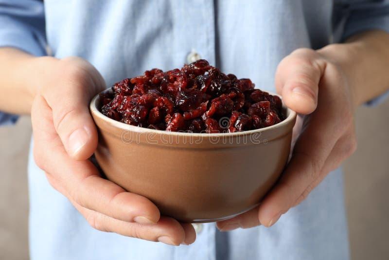 Bacia da terra arrendada da mulher com os arandos saborosos no fundo da cor, close up Frutas secadas imagens de stock