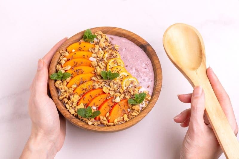 Bacia de Acai com batido, caqui, kumquat, granola e chocolate do mirtilo foto de stock