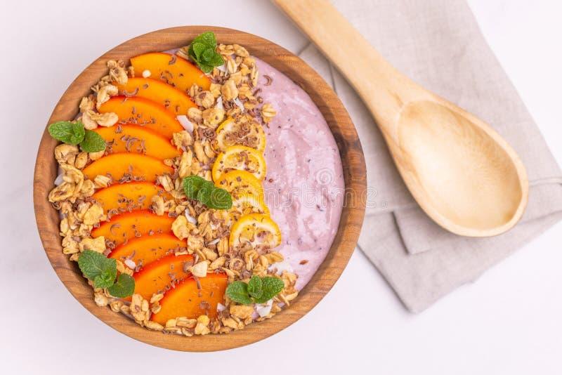 Bacia de Acai com batido, caqui, kumquat, granola e chocolate do mirtilo imagem de stock