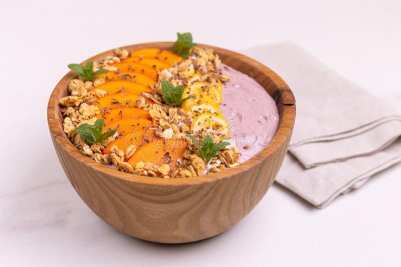Bacia de Acai com batido, caqui, kumquat, granola e chocolate do mirtilo fotografia de stock