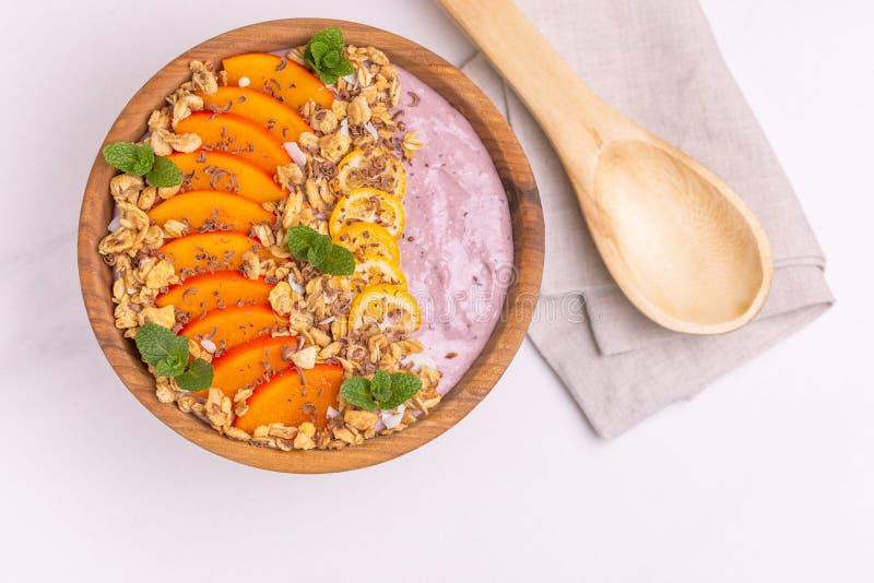 Bacia de Acai com batido, caqui, kumquat, granola e chocolate do mirtilo fotografia de stock royalty free