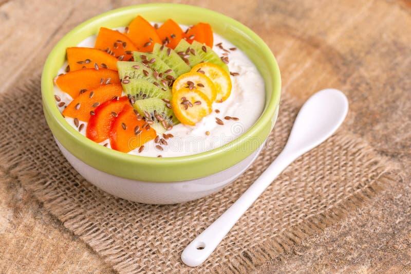 Bacia de Acai com batido, caqui, quivi, kumquat e flaxseeds da baunilha imagens de stock