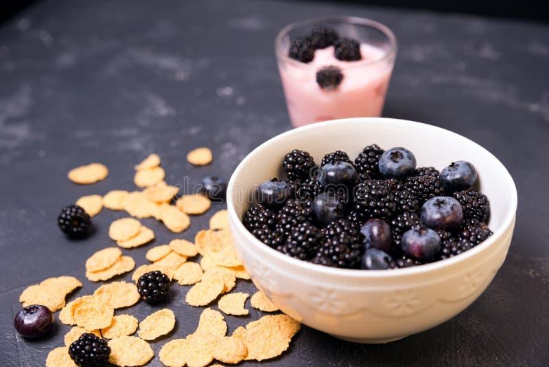 Bacia de amoras-pretas, de mirtilos e de cereal café da manhã natural da manhã imagens de stock