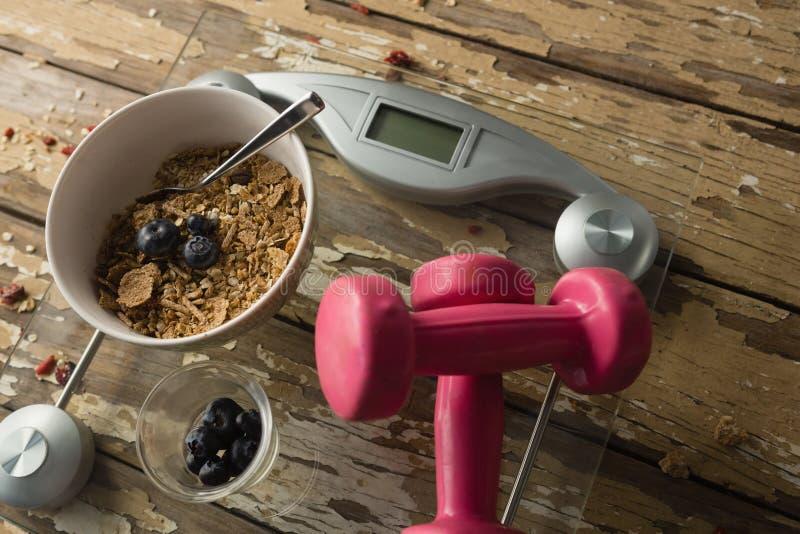 Bacia de café da manhã e de pesos na escala de peso foto de stock