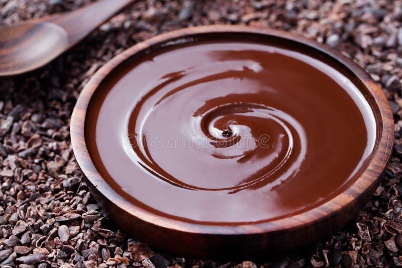 Bacia de chocolate derretido e de colher de madeira em feijões de cacau crus esmagados, espaço da cópia do fundo das pontas imagens de stock royalty free