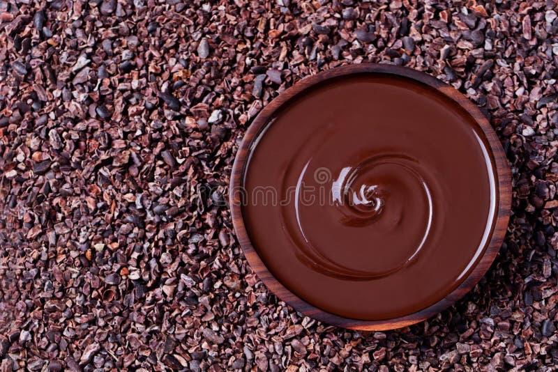 Bacia de chocolate derretido e de colher de madeira em feijões de cacau crus esmagados, opinião superior do espaço da cópia do fu foto de stock