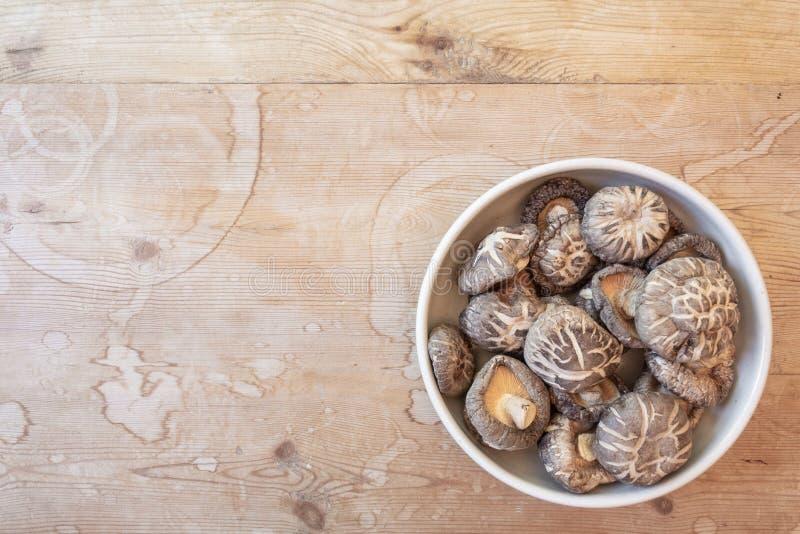 Bacia de cogumelos de shiitake secados, mais baixo direito, em uma tabela de madeira velha, espaço da cópia foto de stock royalty free