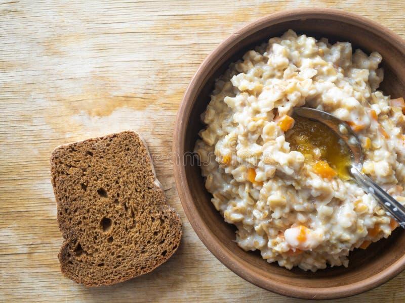 Bacia de farinha de aveia cozinhada com leite, partes da abóbora e flavored com mel imagens de stock