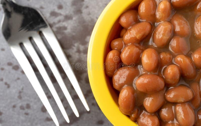Bacia de feijões cozidos com bacon em um molho de tomate em um fundo cinzento com uma forquilha à vista próxima lateral fotografia de stock royalty free