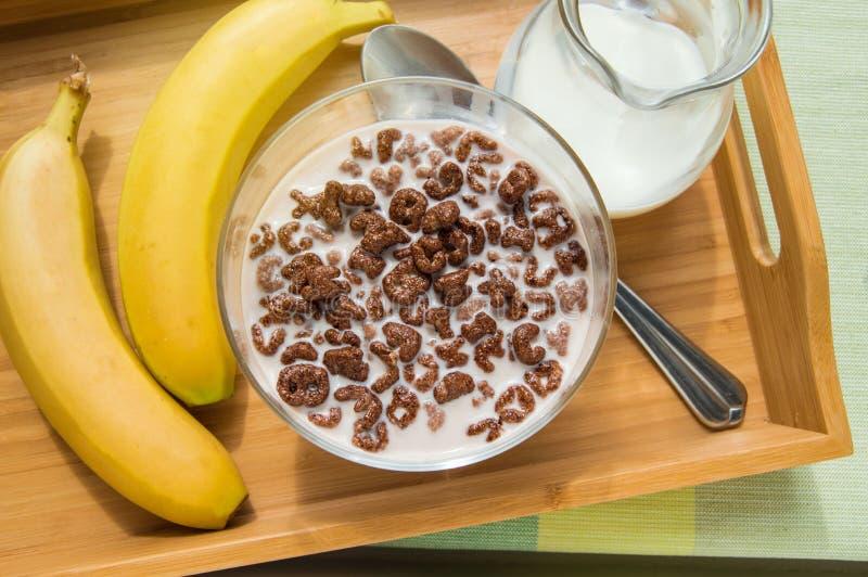 Bacia de flocos do chocolate da farinha de aveia na forma das letras do alfabeto com leite em uma bandeja de madeira com bananas  fotografia de stock royalty free