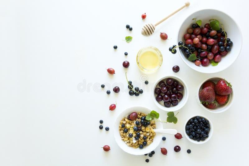 Bacia de granola caseiro com morango, mirtilo, cereja, groselha, o corinto preto e o mel no fundo de madeira branco liso fotos de stock