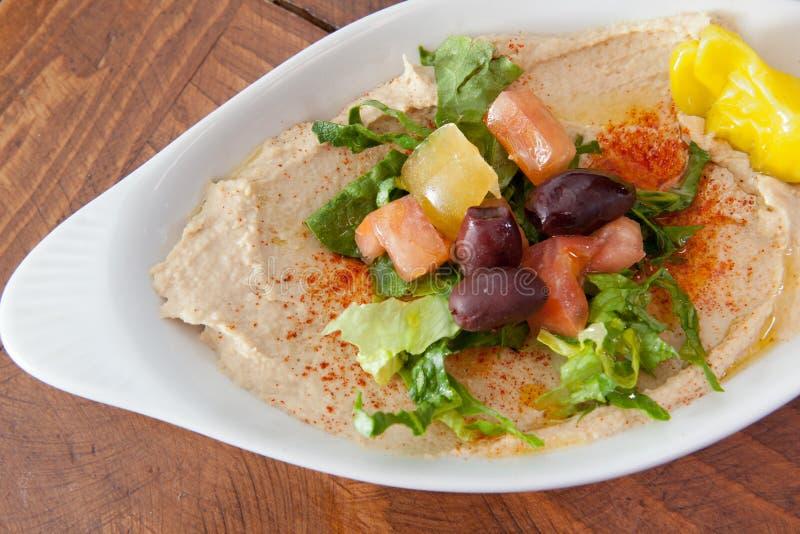 Bacia de hummus coberta com salada imagem de stock royalty free