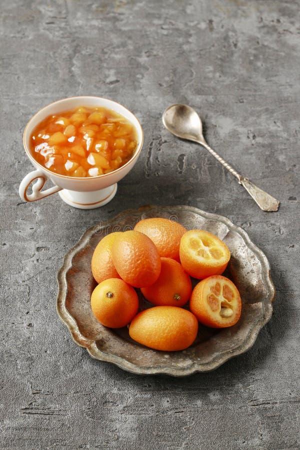A bacia de kumquats maduros e o copo da porcelana com kumquat bloqueiam foto de stock royalty free