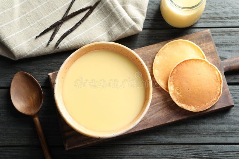 Bacia de leite condensado e de panquecas servidos na tabela de madeira, vista superior imagens de stock