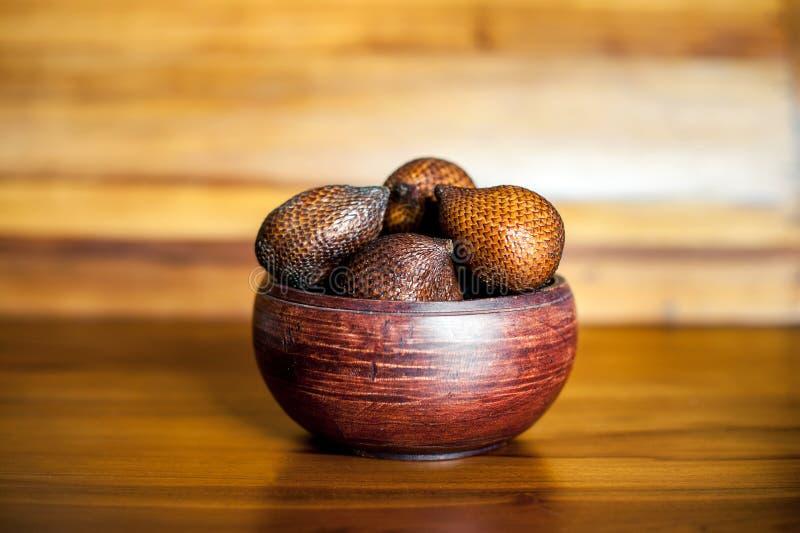 A bacia de madeira de Brown com salak ou serpente frutifica Frutos frescos exóticos de Bali, Indonésia fotografia de stock royalty free