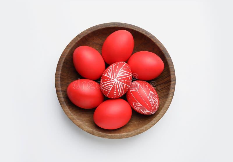 Bacia de madeira com os ovos da páscoa vermelhos pintados no fundo branco fotografia de stock royalty free