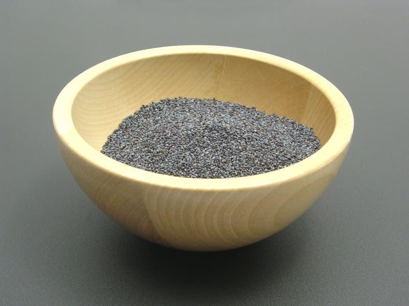 Bacia de madeira com sementes de papoila imagem de stock