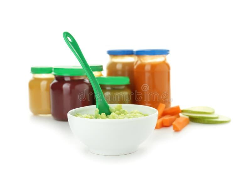 Bacia de puré vegetal e de frascos saudáveis com comida para bebê no fundo branco imagens de stock royalty free