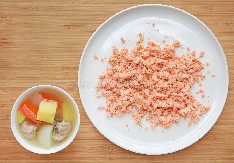 Bacia de sopa do osso da carne de porco da cenoura, da cebola e da batata com os peixes Shredded dos salmões na placa branca no f fotografia de stock royalty free
