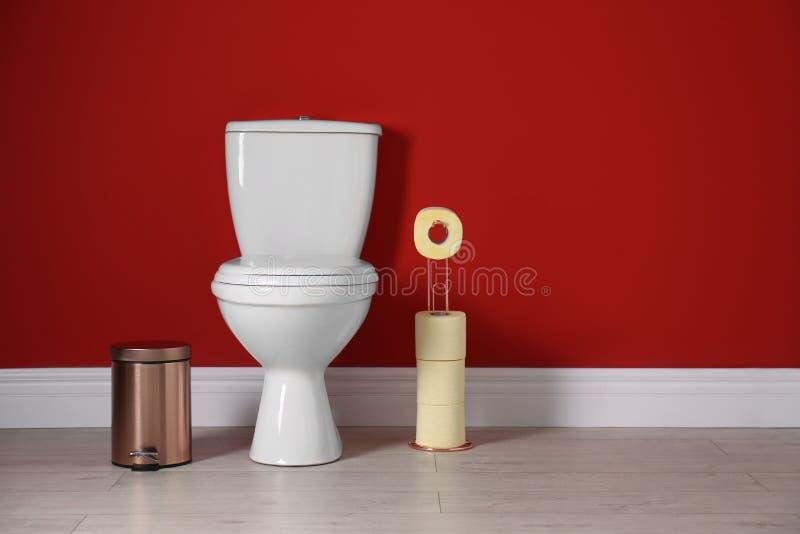 Bacia de toalete com rolos de papel e escaninho de lixo no toalete imagem de stock