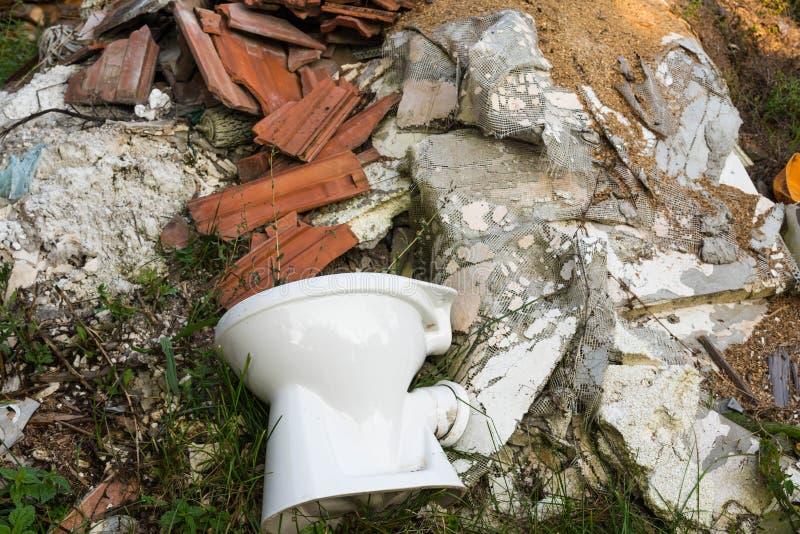 Bacia de toalete no fim enorme do desperdício da construção acima do tiro fotos de stock