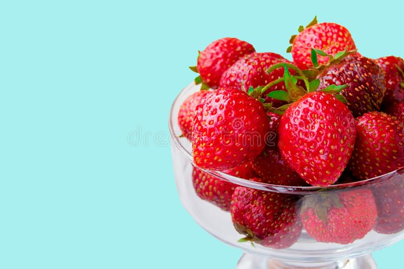 Bacia de vidro com as morangos maduras frescas, espa?o para o texto, espa?o da c?pia isolado no fundo azul, disposi??o, grampeame fotos de stock royalty free