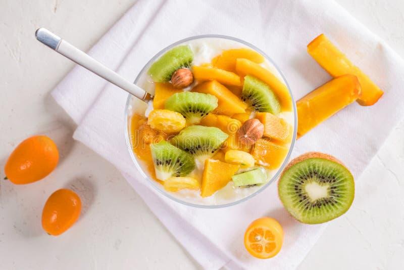 Bacia de vidro do close-up com iogurte e colher cortada do fruto e a metálica no guardanapo branco fotos de stock