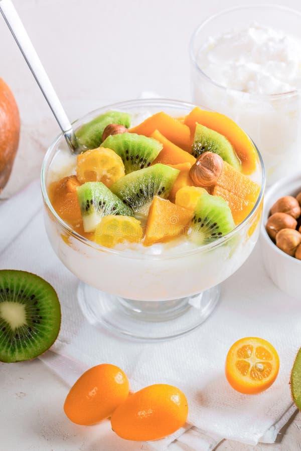 Bacia de vidro do close-up com iogurte e frutos no guardanapo branco imagem de stock royalty free