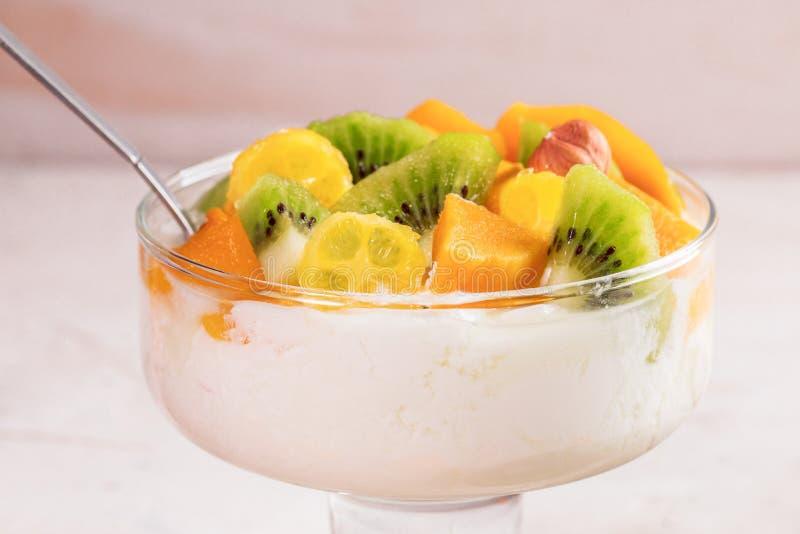 Bacia de vidro do close-up na haste com iogurte e frutos frescos cortados no fundo branco imagem de stock royalty free