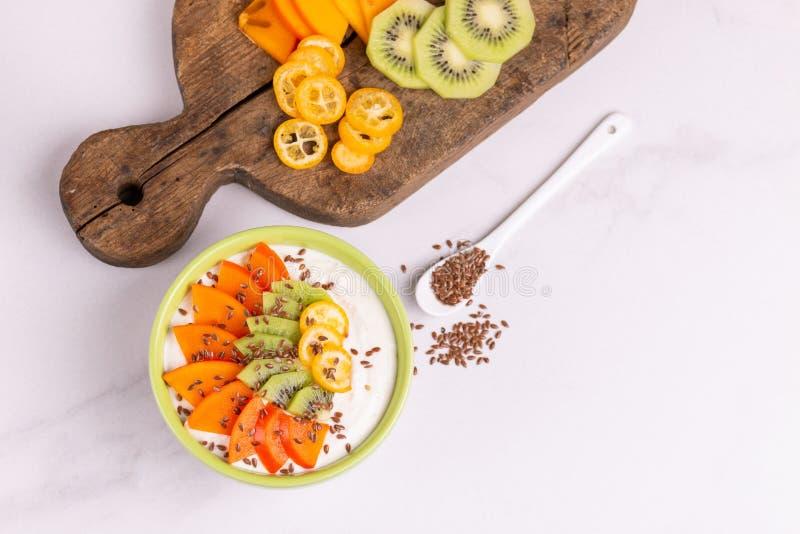 Bacia do acai da baunilha com as sementes do caqui, do quivi, do kumquat e de linho fotografia de stock royalty free
