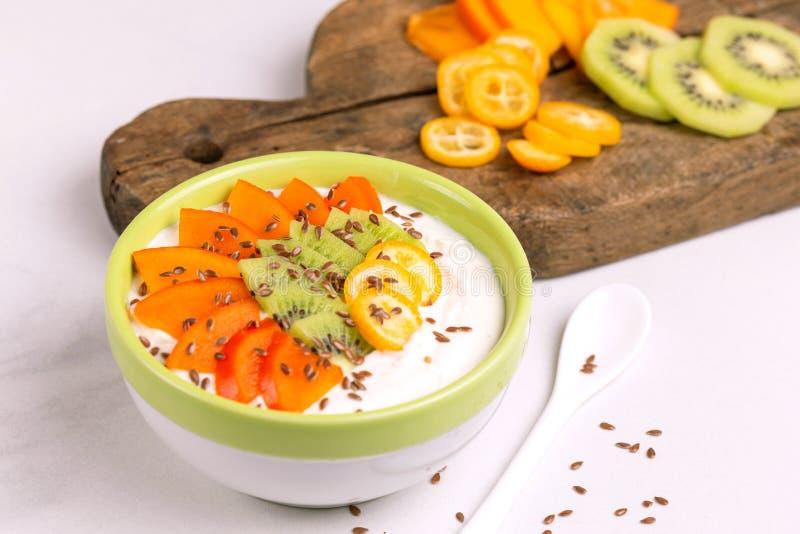 Bacia do acai da baunilha com as sementes do caqui, do quivi, do kumquat e de linho imagem de stock royalty free